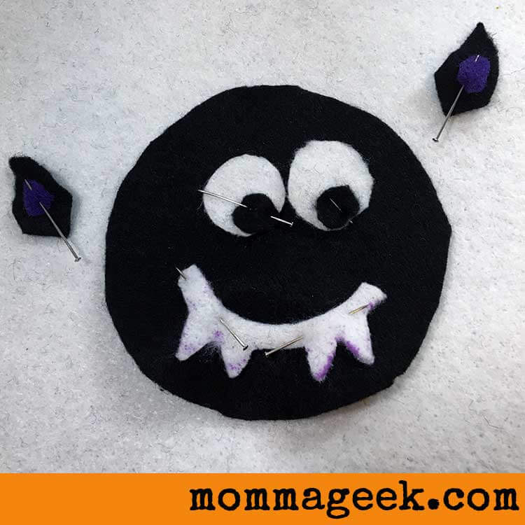 Pin the pieces of felt to the black bat face